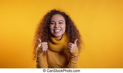 Winner. Success. Positive girl making thumbs up sign over yellow background and smiles to camera. Body language. Young mixed race curly woman