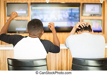 Closeup portrait, two men watching a sports game on tv. One guy rejoices, other guy feels terrible. Team spirit concept