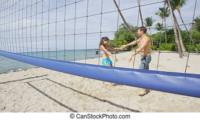 Winning cheering beach volleyball players high five celebrating win having fun together. People playing beach volley. Woman and man winning recreational volley ball together cheering. SLOW MOTION.