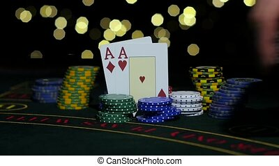 Winning hand of playing cards on poker table, pile of chips, winner's gain. Close up. Slow motion