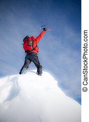 Mountaineer reaches the top of a mountain peak and expresses his joy. Vertical frame. Soft-focus version