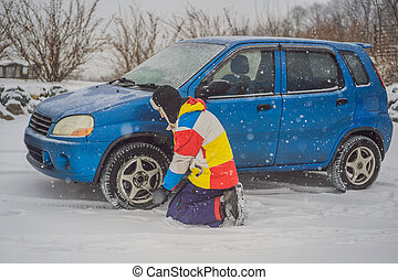 Winter accident on the road. A man changes a wheel during a snowfall. Winter problems