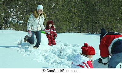 Winter activities - Family making a snowman together, mom...