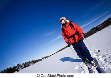 Winter Advture Skiing - A woman cross country skiing across...