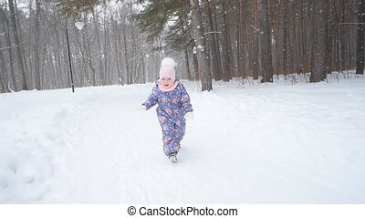 Winter and Christmas concept. Happy little girl playing with snow in a winter park