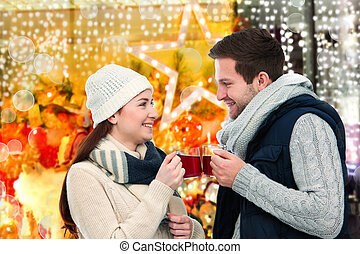 Winter and Christmas time - Romantic young couple drinking...