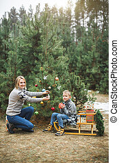 Winter and people concept - mother with child son decorates a christmas tree outdoors in the forest. The boy is sitting on the wodden sledge and drinking hot drink