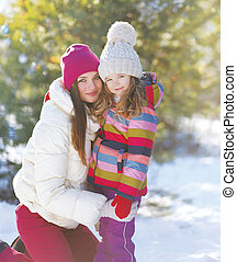 Winter and people concept - portrait of a mother and child in th