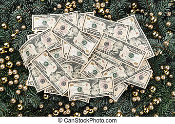 Winter background of fir branches. Adorned with gold baubles. Christmas card. Top view. Xmas congratulations. A lot of money in the middle