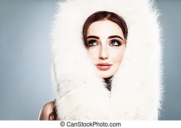 Winter Beauty. Beautiful Winter Woman with Makeup and White Fur Looking Up
