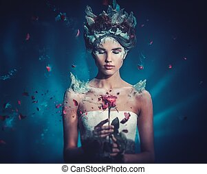 Winter beauty fantasy woman portrait. Beautiful young model girl and blast of frozen rose.