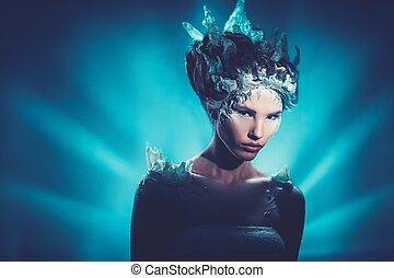 Winter beauty fantasy woman portrait. Beautiful young model girl with frozen fashion makeup and hairstyle.