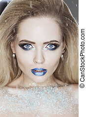 Winter Beauty Woman. Christmas Girl Makeup. Holiday Make-up. Snow Queen High Fashion Portrait over Blue Snow Background. Eyeshadows, False Eyelashes and Crystals on the Lips.