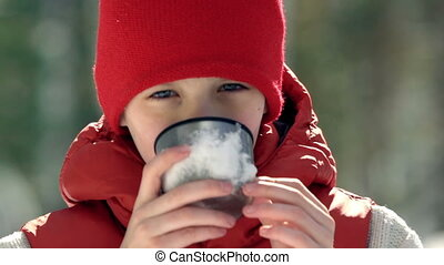 Winter Beverage - Portrait of teenage boy sipping from snowy...