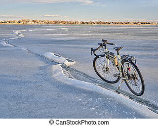 winter biking, touring or commuting - bicycle on a frozen lake, Boyd Lake State Park in northern Colorado