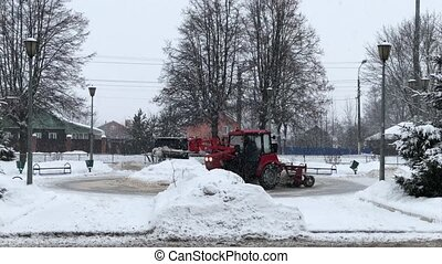 winter blizzard tractor cleans snow in the city - winter...