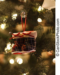 Winter boots Christmas ornament on pine tree