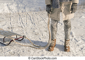 Winter boots on snow near sledge with rope.