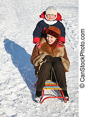 winter child with mother on sled