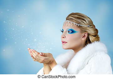 Winter Christmas Girl. Beautiful Woman Blowing Snow
