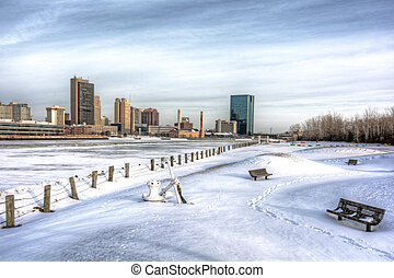 A view of downtown Toledo Ohio's skyline from across the frozen and snow covered Maumee river. A beautiful partly cloudy blue sky makes for a pretty winter scene.