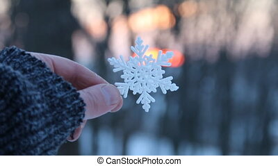 winter concept, hand holding a snowflake at sunset in the winter forest