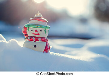 Winter concept with snowman on snow background.