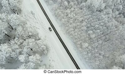 winter country road in a snowy forest, aerial view with drone