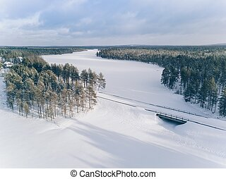 Winter country road on the bridge across frozen lake. Aerial view