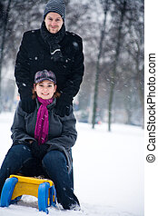 Winter couple on a sled - Happy couple in the snow having...