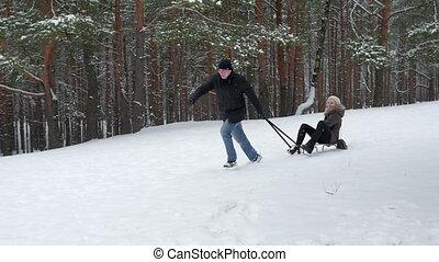 Winter couple sledding together, slow motion 96fps