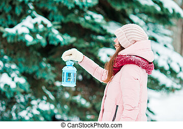 Winter day. Woman holding Christmas lantern outdoors on beautiful winter snow day
