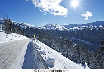 Winter Drive in Colorado. Mountain Road Covered by Snow and...