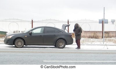 Winter Driving. Car Trouble. A troubled young man rummaging in the trunk