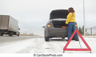 Winter Driving. Car Trouble. An emergency sign. Car trouble on a snowy country road. A young woman call the rescue service