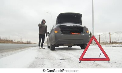 Winter Driving. Car Trouble. Car trouble on a snowy country road. A young man call the rescue service