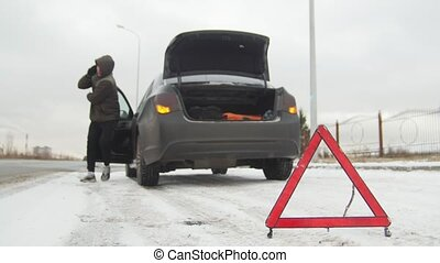 Winter Driving. Car Trouble. Car trouble on a snowy country road. A young man walks out of the car