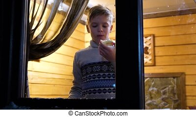 Winter evening. In a warm and bright room near the window stands a young man. Shooting outdoors.