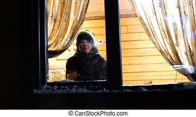 Winter evening. In a warm and bright room near the window stands a young man. throwing a snowball In window