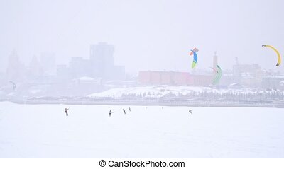 Winter extremal sport - a lot of snow-kite sportsmen's rides on the ice river at blizzard cloudy day