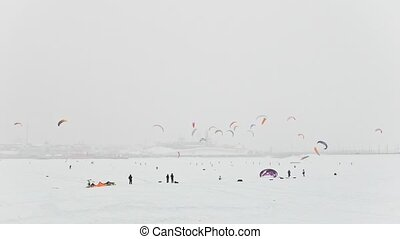Winter extremal sport - a lot of colorful snow-kites over the ice river in front of city at blizzard cloudy day