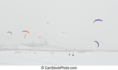 Winter extremal sport - colorful snow-kites over the ice river in front of city at blizzard cloudy day