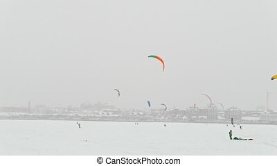 Winter extremal sport - colorul snow-kites on the ice river in front of city at blizzard cloudy day