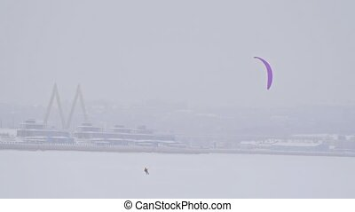 Winter extremal sport - snow kiting on the ice river in front of city at cloudy snowfall day