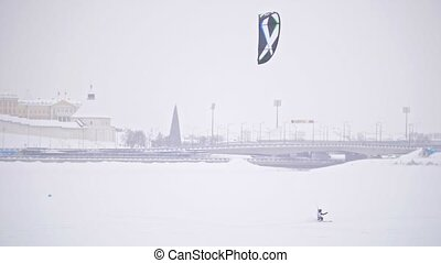 Winter extremal sport - snow kiting on the ice river in front of city