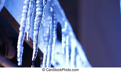 Huge icicles on a house roof.