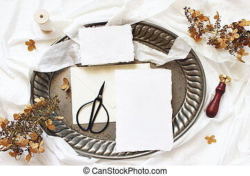 Winter, fall wedding, birthday table composition. Stationery mockup scene. Greeting cards, envelope, dry hydrangea flowers and silk ribbon on old vintage tray. White silk fabric background.