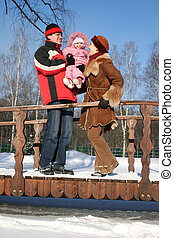 winter family with baby on bridge