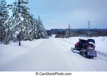 Winter Finnish snowy lanscape with road and snowmobile