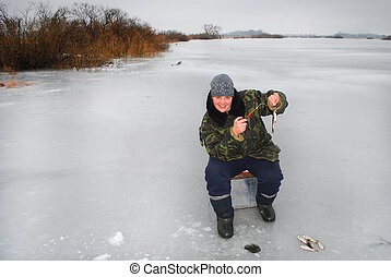 Winter fisherman on the river catching fish